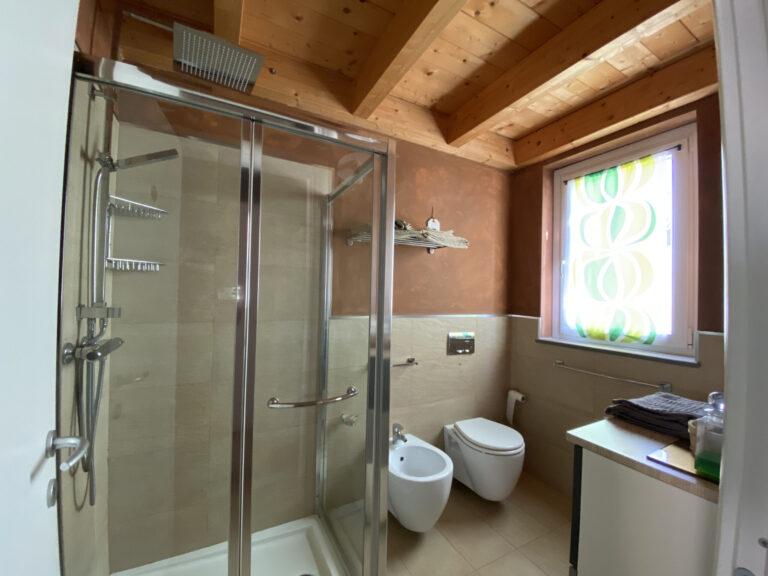 bagno del b&b con ampia doccia e tetto in legno