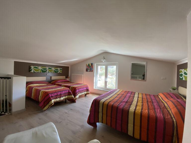 camera quadrupla con 4 posti letti con coperte colorate
