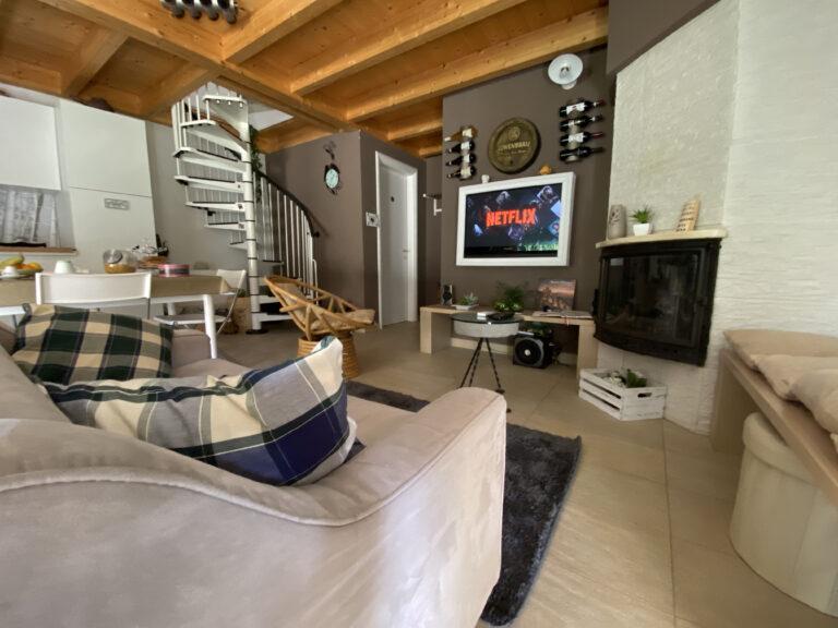 salone piccolo e funzionale con caminetto tv e divano due posti